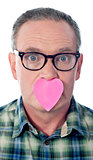 Surprised aged male with paper heart over his mouth