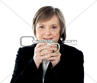 Old woman holding coffee mug