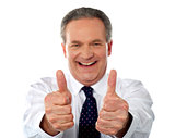 Happy businessman gesturing double thumbs-up