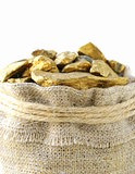 gold nuggets in a linen bag on a white background