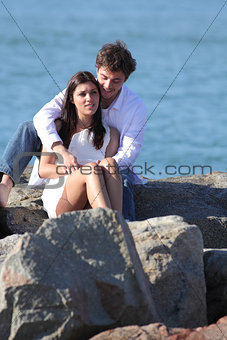 Affectionate couple flirting and hugging on a stone on the beach