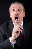 Businessman holding index finger at his mouth