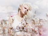 Blossom. Beauty Blonde in Windy Field with Flowers. Nature. Springtime