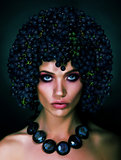 Portrait of Autumn Woman with Grapes on her Head. Trendy Hairstyle