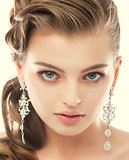 Jewelry. Portrait of Gorgeous Exquisite Woman with Shiny Earrings. Refinement