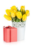 Yellow tulips in a vase and red gift box