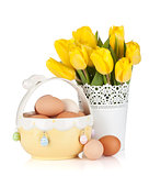 Fresh yellow tulips and eggs in bowl