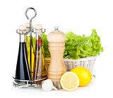 Lettuce in basket with lemon fruits, pepper shaker, olive oil an