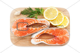 Salmon steaks with herbs and lemon slices on cutting board