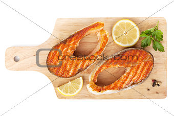 Grilled salmon with lemon slices and herbs on cutting board