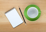 Empty coffee cup, notepad and pencil