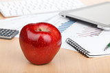 Ripe red apple on workplace