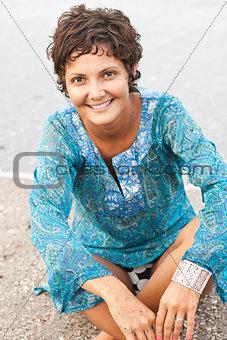 brunet woman in blue dress on the beach