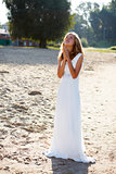 Praying girl bride in a white dress on the sunny outdoor