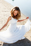Elegant young girl bride in a white dress on a sandy river beach