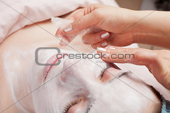 Silk mask applying, beauty treatment young woman face at salon