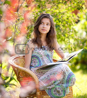 Girl reading book sitting in wicker chair outdoor in summer day