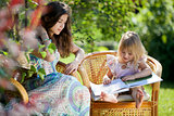 Girls reading book sitting in wicker chairs outdoor in summer da
