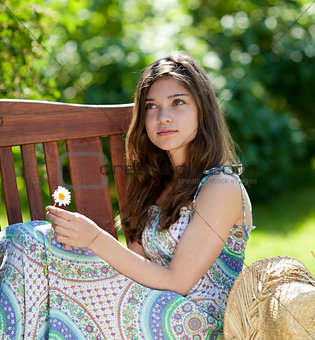 Girl with camomile flower sitting outdoor in summer day