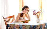 Pensive girl with book sitting at table indoor in summer day wit