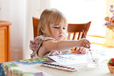 Little girl painting picture with watercolour
