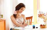 girl writing at table by pen and ink indoor in summer day with s