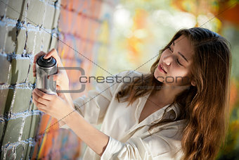 teenage girl portrait with spray can near graffiti wall