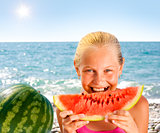Girl eating watermelon on seashore