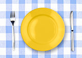 Knife, yellow plate and fork on yellow checked tablecloth