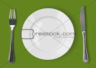 Knife, white plate and fork on green background