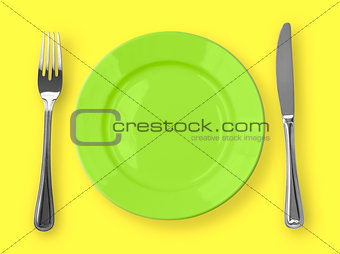 Knife, green plate and fork on yellow background