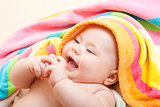 Adorable happy baby in colorful towel after bath