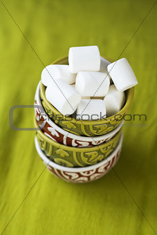 Four oriental national bright bowls on a green background and white marshmallows