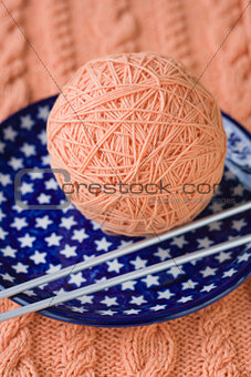 One ball of pink yarn and knitting needles on a blue plate with stars