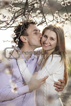 Young romantic couple in spring blossom