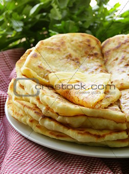 pile of fried bread with butter and parsley