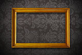 golden vintage empty frame on dark floral wallpaper