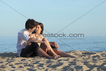 Couple flirting sitting on the sand of the beach