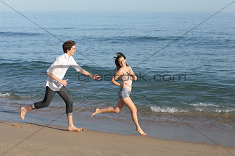 Couple playing and running on the beach
