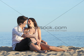 Couple sitting and laughing on the sand of the beach