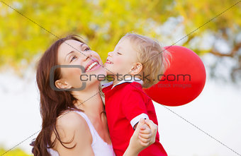 Little boy kissing mom
