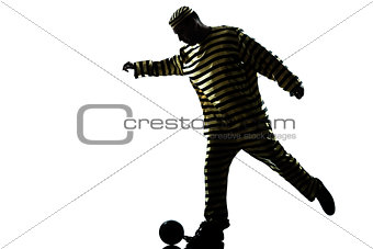 man prisoner criminal playing soccer with chain ball