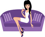 Young woman with a wine glass sits on a sofa