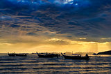 Ocean coast cloudy colorful sunset with fishing boats