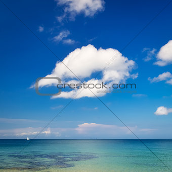 Ocean landscape with blue cloudy sky and little sailboat