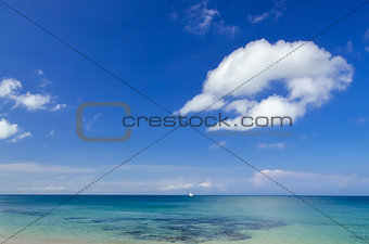 Ocean landscape with blue cloudy sky and sailboat