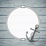 Nautical card with frame of the rope and anchor on wooden background.