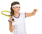 Smiling female tennis player with racket pointing on copy space