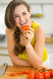 Smiling young woman eating tomato