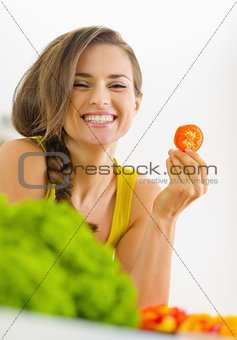 Portrait of happy young woman with tomato in kitchen
